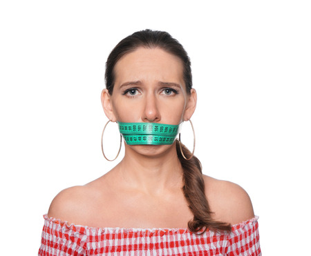 Woman with measuring tape around her mouth on white background. Diet concept