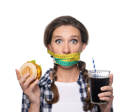 Emotional woman with measuring tapes around her mouth and unhealthy food on white background. Diet concept