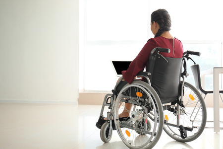 Asian woman in wheelchair working with laptop in office Foto de archivo