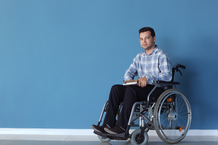 Young man in wheelchair near color wall