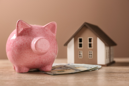 Cute piggy bank with money and house model on table