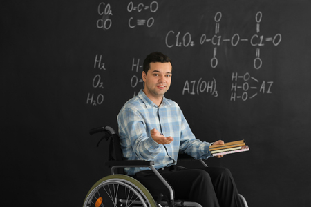 Male teacher with books in wheelchair near chalkboard