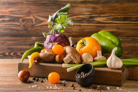 Wooden board with various fresh vegetables and spices on wooden table