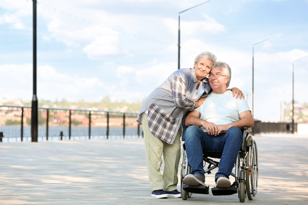 Senior man in wheelchair and his wife outdoors