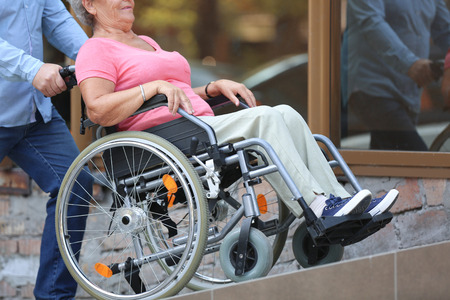 Senior woman in wheelchair and her husband on ramp outdoors Stock Photo