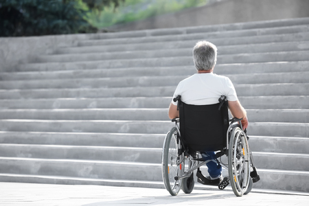 Senior man in wheelchair near stairs outdoors