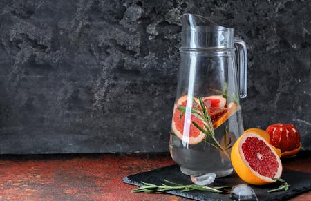 Glass jug with refreshing grapefruit lemonade on table 免版税图像