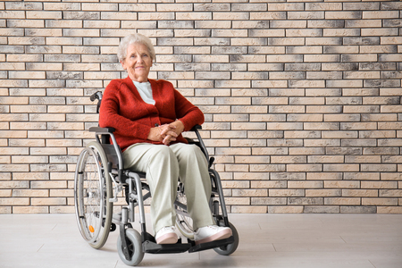 Senior woman in wheelchair against brick wall Banque d'images - 115056122