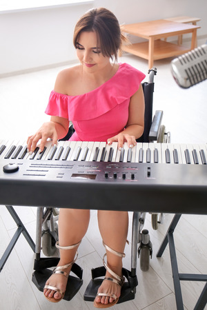Beautiful young musician in wheelchair playing synthesizer at home