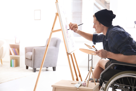 Young artist in wheelchair painting picture at home Imagens