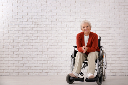 Senior woman in wheelchair against white brick wall Stock Photo