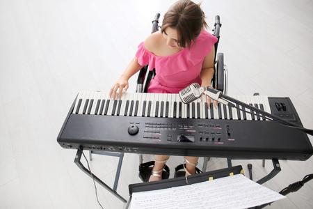Schöner junger Musiker im Rollstuhl, der zu Hause Synthesizer spielt