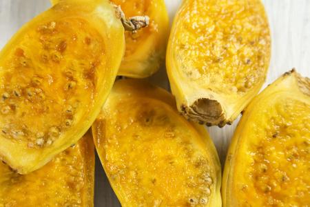 Halves of ripe cactus pears on table