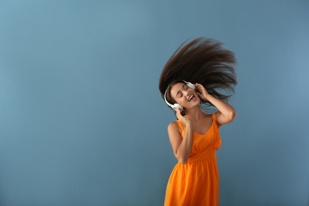 Beautiful young woman listening to music on color background Standard-Bild