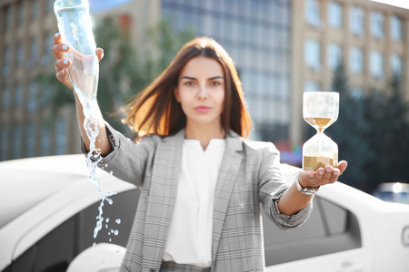 Young businesswoman holding empty bottle and hourglass outdoors. Time management concept