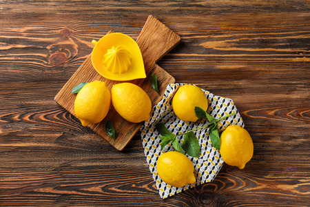 Whole ripe lemons and juicer on wooden table Imagens