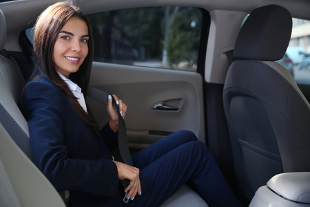 Young businesswoman fastening safety belt in car 版權商用圖片