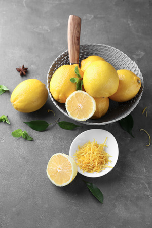 Wicker bowl with ripe lemons and fresh zest on grey table