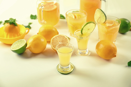 Glasses of fresh lemon juice on light table