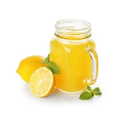Mason jar of fresh lemon juice on white background
