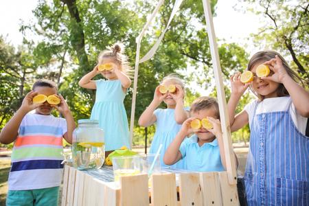 Little children playing while preparing fresh lemonade in park Stockfoto