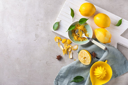 Composition with ripe lemons and zest on grey table
