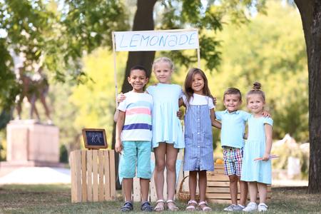Little children near lemonade stand in park Фото со стока