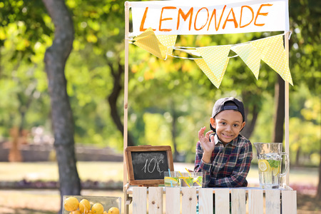 Little African-American boy at lemonade stand in park Фото со стока