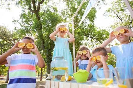 Little children playing while preparing fresh lemonade in park