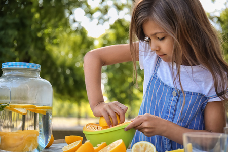 Little girl preparing fresh lemonade in park Stockfoto