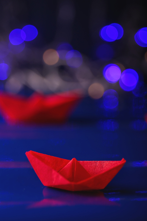 Origami boat against blurred lights