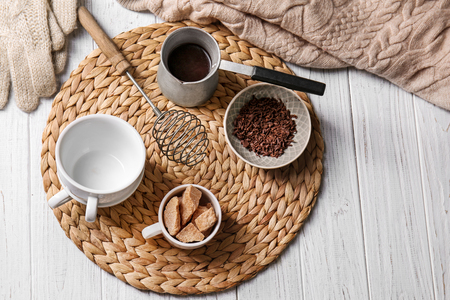 Cezve of hot chocolate with ingredients on wicker mat Stock fotó