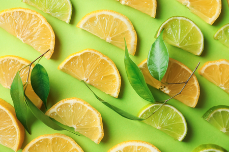 Composition with slices of ripe lemon and lime on color background