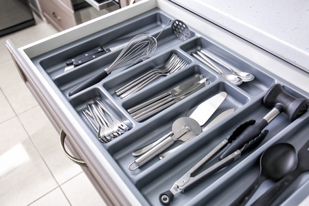 Set of clean kitchen utensils in drawer