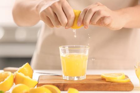 Femme pressant du jus de citron frais dans un verre à table Banque d'images