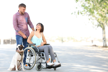 Young woman in wheelchair with her husband and service dog outdoors Imagens