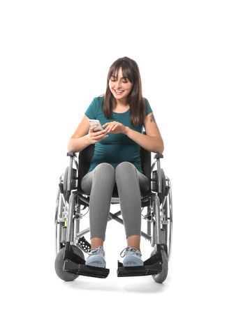 Young woman in wheelchair with mobile phone on white background Imagens