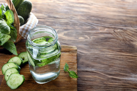 Jar of cucumber infused water on wooden table Stok Fotoğraf