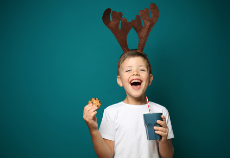 Cute little boy with toy reindeer horns holding cup of hot chocolate and cookie on color background 版權商用圖片