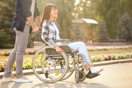 Young woman in wheelchair and her husband outdoors