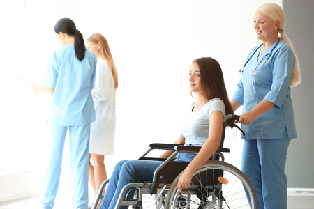 Handicapped young woman with mature female doctor in clinic