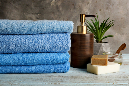Clean soft towels with cosmetics on light wooden table