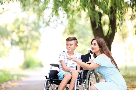 Teenage boy in wheelchair with his mother outdoors