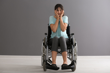 Depressed young woman in wheelchair against grey wall
