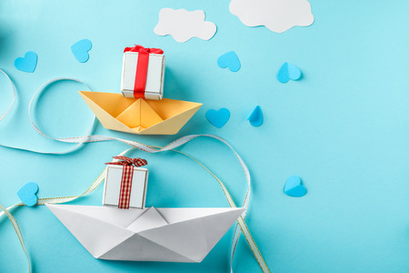 Composition with origami boats and gifts on color background