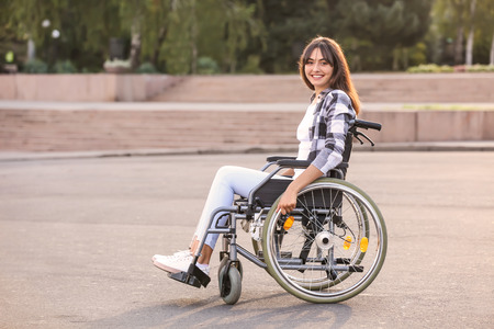 Happy young woman in wheelchair outdoors