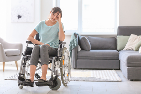 Depressed young woman in wheelchair at home