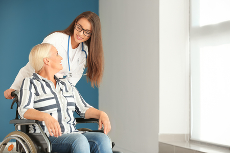 Handicapped mature woman with young female doctor in clinic Imagens