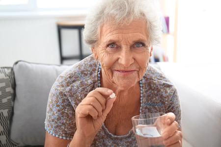 Senior woman taking medicine at home