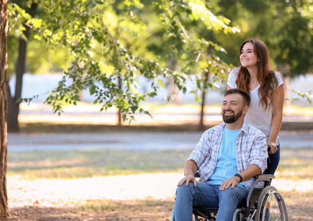 Young man in wheelchair with his wife walking outdoors Imagens